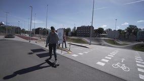 Elektrischer Longboard-Mann im grünen Hemd und Hut fahren auf rotes Sportstadion mit Spielplatz stock footage