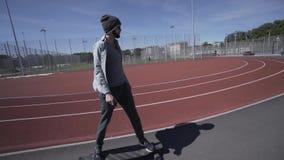 Elektrischer Longboard-Mann im grünen Hemd und Hut fahren auf rotes Sportstadion mit Spielplatz stock video