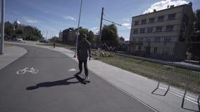 Elektrischer Longboard-Mann im Sweatshirt und Hut fahren auf rotes Sportstadion mit Spielplatz stock video