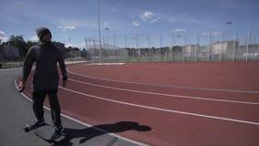 Elektrischer Longboard-Mann im Sweatshirt und Hut fahren auf rotes Sportstadion mit Spielplatz stock footage