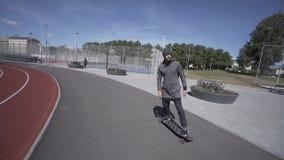 Elektrischer Longboard-Mann im Sweatshirt und Hut fahren auf rotes Sportstadion mit Spielplatz stock video footage