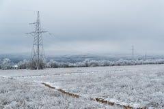 Elektrischer Pfosten auf dem Hintergrund einer Winterlandschaft Stockbild