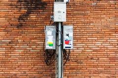 Elektrischer Pfosten mit schmutzigem elektrischem Schaltkasten und Kabel, Ziegelstein Lizenzfreies Stockfoto