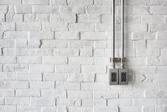 Elektrischer Sockel auf einer Weiß gemalten Backsteinmauer Stockbild