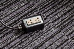 Elektrischer Sockel mit Netzsteckerkabel auf Teppichboden für Safe Stockfoto