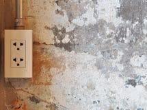 Elektrischer Stecker auf Schmutzzement-Wandhintergrund Stockfotos