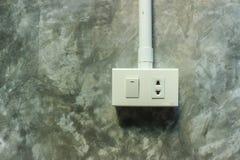 Elektrischer Stecker und Schalter auf grauer Wand Lizenzfreie Stockfotos