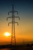 Elektrischer Turm bei Sonnenuntergang mit Sonne Stockfotografie