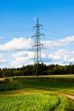 Elektrischer Turm mit Stromleitungen auf einem Gebiet unter einem blauen Himmel lizenzfreies stockfoto