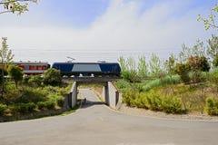 Elektrischer Zug, der hinter Eisenbahnbrücke an conuntryside Zinn beschleunigt Lizenzfreie Stockfotografie