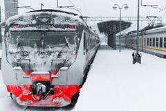 Elektrischer Zug im Schnee in einem Blizzard auf einer leeren Plattform Lizenzfreie Stockfotografie