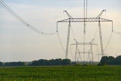 Elektrisches Netz auf Hintergrund des Himmels und des grünen Feldes lizenzfreies stockbild
