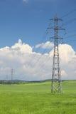 Elektrisches Netz der Pole auf einem grünen Met Lizenzfreie Stockfotografie