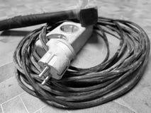 Elektrisk förlängning och hammare på det belade med tegel golvet arkivfoton