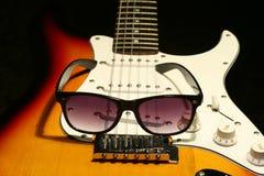 Elektrisk gitarr för tappning med solglasögon på svart bakgrund Arkivbilder