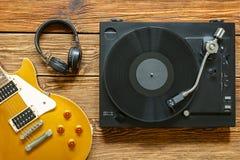 Elektrisk gitarr, hörlurar och skivtallrik med vinyl på träbakgrund Arkivfoton