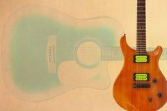 Elektrisk gitarr med gröna uppsamlingar och akustisk jumbogitarr på krämig pappbakgrund, med överflöd av kopieringsutrymme royaltyfri fotografi