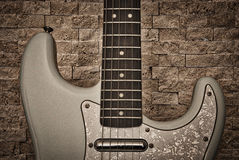 Elektrisk gitarr mot den sten texturerade väggen Fotografering för Bildbyråer