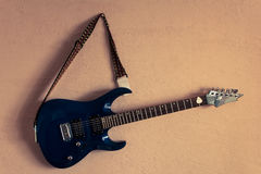 Elektrisk gitarr på en bakgrund av tappningbeigaväggen Arkivbild