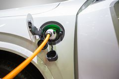Elektrisk hybrid- bil som är inkopplings in till uppladdaren till laddande elkraft till batteriet att reservera energi arkivbild
