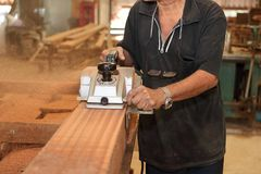 Elektrisk hyvlare som rakar ett stycke av träbrädet med händer av den höga snickaren i snickeriseminarium Den selektiva fokusen o royaltyfri foto