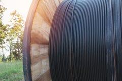 Elektrisk kabel för svart tråd med träspolen av elektrisk kabel Royaltyfri Foto