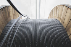 Elektrisk kabel för svart tråd med träspolen av elektrisk kabel Arkivfoto