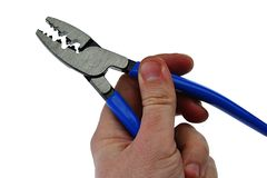 Elektrisk krusa avklädningplattång med det blåa rubber handtaget som rymms i vänster hand av den vuxna manliga personen, öppnade  Arkivbild