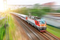 Elektrisk lokomotiv med passagerarebilar som passerar stångvägen till och med staden på den soliga dagen för hastighetsrörelse royaltyfri fotografi