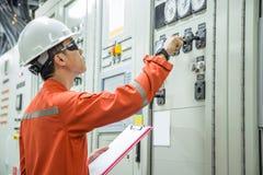 Elektrisk och instrumenttekniker som kontrollerar elektricitetssystemet royaltyfria bilder