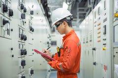 Elektrisk och instrumenttekniker som loggar data i elektriskt rum för strömbrytarekugghjul royaltyfri foto