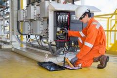 Elektrisk och instrumenttekniker som mäter spänning av thermo elektriskt generator- och rekordläsningvärde royaltyfri bild