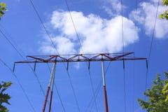 Elektrisk pylon, hög spänningslinje på en blå sky Royaltyfri Fotografi