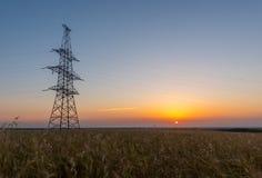 Elektrisk pylon på vetefält på soluppgång Fotografering för Bildbyråer