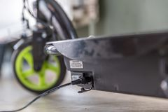 Elektrisk sparkcykel för Closeupdagsikt som laddar upp Arkivbild