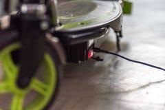 Elektrisk sparkcykel för Closeupdagsikt som laddar upp Arkivfoto