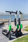 Elektrisk sparkcykel för LIMEFRUKT på trottoarerna Royaltyfria Bilder