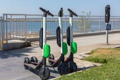 Elektrisk sparkcykel för LIMEFRUKT på trottoarerna Royaltyfri Foto
