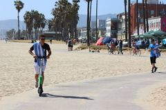 Elektrisk sparkcykel för ung grabbridning på den Venedig stranden Fotografering för Bildbyråer