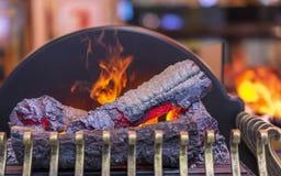 Elektrisk spis med efterföljd av flamman och vedträt arkivbild