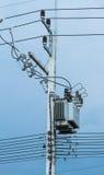 Elektrisk stolpe vid vägen med kraftledningkablar, transformatorer och telefonlinjer Arkivbilder