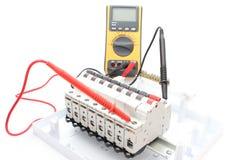 Elektrisk strömbrytare på kontrollbordet och multimeteren Arkivfoto