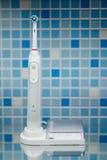 Elektrisk tandborste på blåtttegelplattabakgrund Royaltyfria Bilder