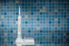 Elektrisk tandborste på blåtttegelplattabakgrund Royaltyfri Fotografi