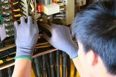 Elektrisk terminal i föreningspunktask och service av teknikeren Den elektriska apparaten installerar i kontrollbordet för servic royaltyfri bild