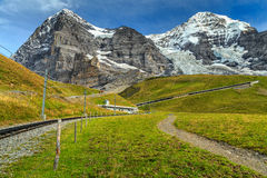 Elektrisk trailway och Eiger norr framsida, Bernese Oberland, Schweiz, Europa Fotografering för Bildbyråer