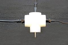 Elektrisk utslagsplats med en plugga som sätts in i binda arkivbild