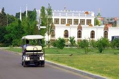 Elektrisk vagn som kör längs asfaltvägen förbi grön gräsmatta royaltyfria bilder