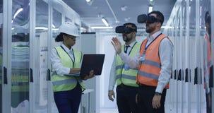 Elektriska arbetare i reflekterande västar genom att använda VR arkivbild