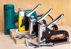 Elektriska häftapparater och manuellt mekaniskt - för reparationsarbete i huset och på möblemang och konsoler arkivbilder
